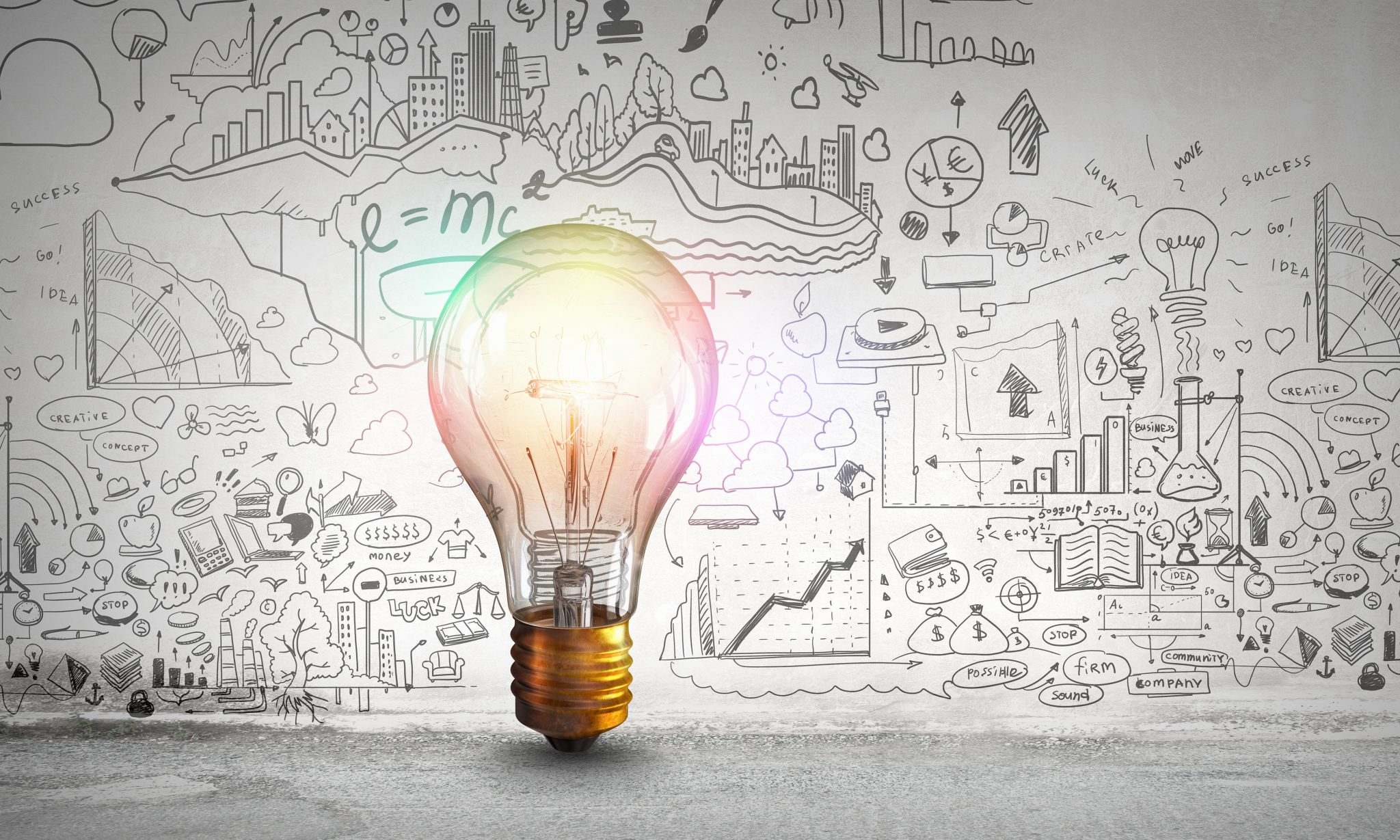 Glowing light bulb and business ideas sketch
